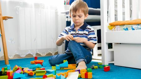 Portrait of little concentrated boy palying on carpet with toy blocks
