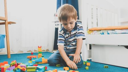 Toned photo of little smiling boy playing with constructor blocks in his bedroom 写真素材