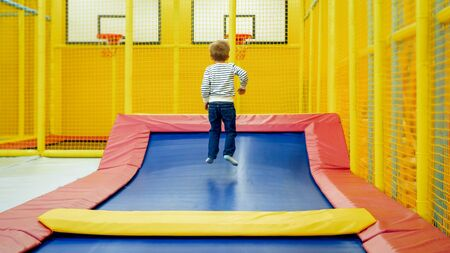 Rear view photo of little boy jumping and having fun on trampoline at amusement park.
