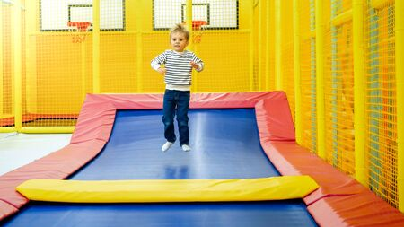 Happy active little boy jumping high on trampoline in palyroom at shopping mall