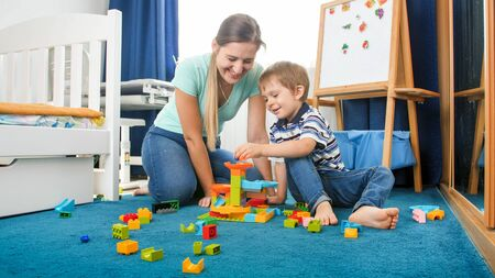Happy smiling mother sitting on floor with her little son and playing with colorful constructro blocks