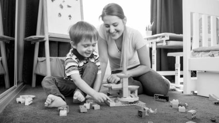 Happy little boy with mother building toy track with blocks and bricks
