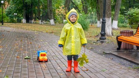 Little toddler boy in raincoat and rubber boots got upset because of bad weather and heavy rain in park