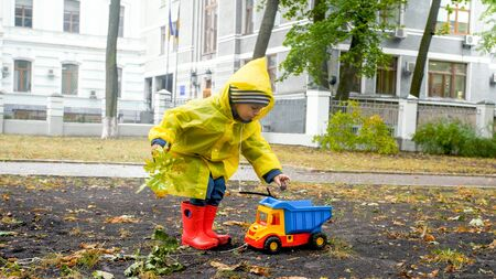 Little boy in raincoat and rubber boots ppicking up fallen autumn leaves and putting it his toy dump truck
