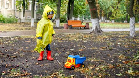 Little toddler boy in raincoat playing with toy truck at park on cold rainy day