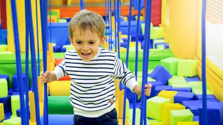Portrait of happy smiling boy playing and climbing on ropes on the playground at amusement park