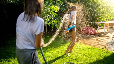 Two teenage girls playing water fight and splashing water from garden hose. Archivio Fotografico