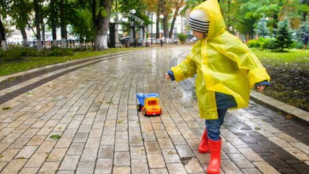 Cute toddler boy in yellow raincoat running with toy truck in rainy autumn park Reklamní fotografie