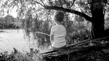 Black and white photo of little boy with wooden fishing rod catching fish on the lake.