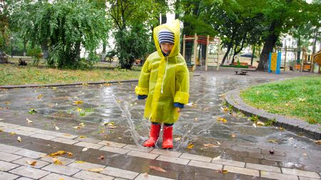 Cute little boy in raincoat and red wellington boots jumping in big puddle at park