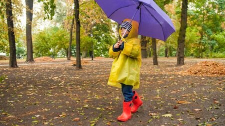 Little toddler boy in wellington booats and raincoat walking at park with umbrella.