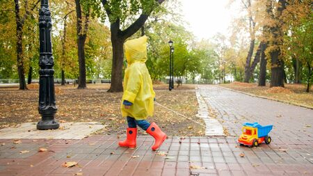 Little boy with toy truck in autumn park on rainy day Archivio Fotografico