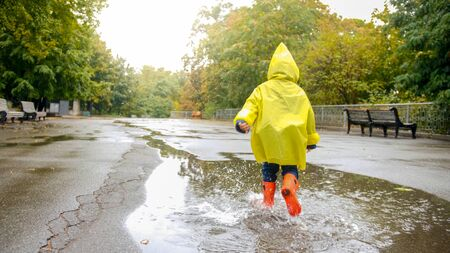 Little happy boy in rubber boots running over big puddle after rain at park
