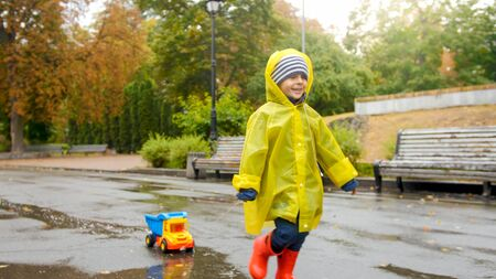 Portrait of smiling cheerful toddler boy running over puddle at park with his toy truck
