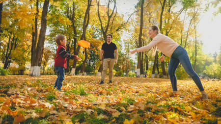 Beautiful young mother throwing flying disc to her little son at autumn park