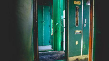 Toned image of open doors in corridor of vintage steam express trian