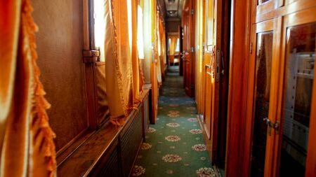 Interior of old wooden train wagon with wooden walls and carpets on floor Archivio Fotografico