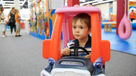 Portrait of little boy driving toy plastic car on playground at shopping mall