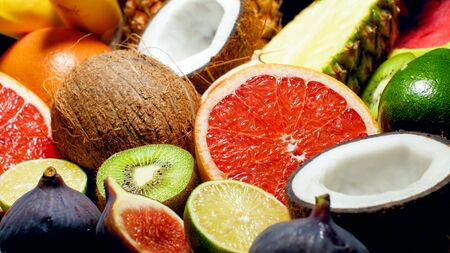 Background of tasty cut tropical and exotic fruits on kitchen table