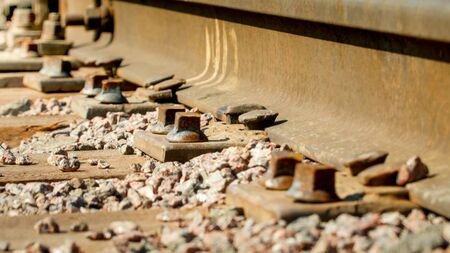 Closeup photo of old rusty nuts and bolts connecting rails to wooden sleepers on railroad