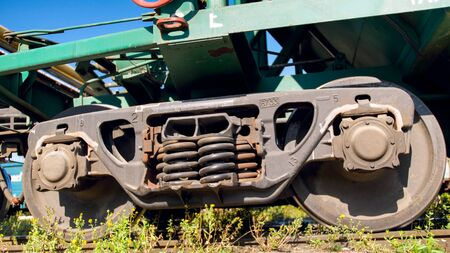 Closeup image of suspension system and metal wheels on cargo train wagon