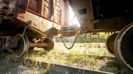 Photo of coupler connecting and pairing two cargo train cars on railroad at susnet