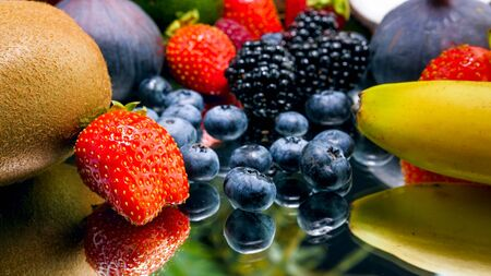 Closeup photo of fresh tasty berries and fruits lying on mirror surface