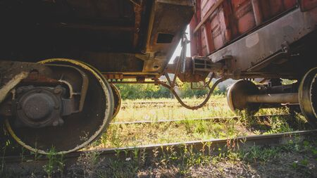 Two old rusty train cars connected with rusty coupler on railway