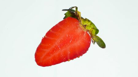 Macro image of cut strawberry in half over white background. Abstract background of berries and fruits.