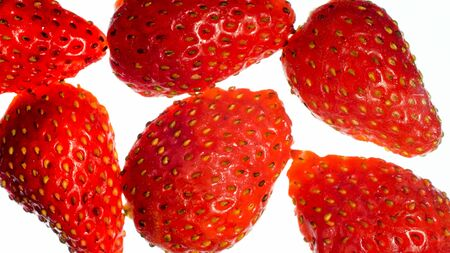 Macro isolated photo of ripe sweet red strawberries over white backgorund. Abstract background of berries and fruits.