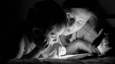 Black and white portrait of little toddler boy reading book with mother lying under blanket at night
