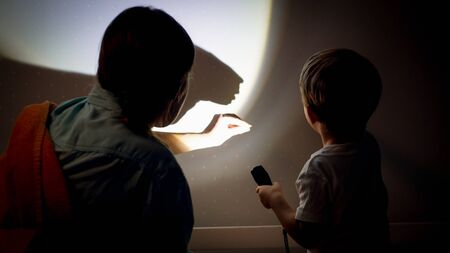 Closeup image of young mother teaching her little son showing shadows from torch on wall at night
