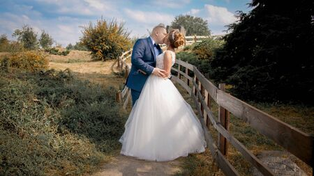 Toned image of newly married bride and groom kissing at long wooden fence at countryside