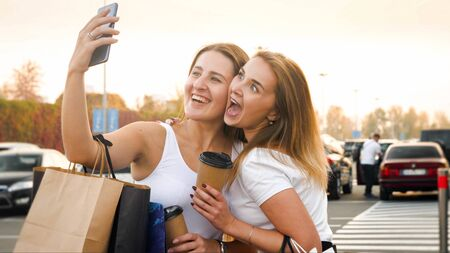 Portrait of two girls smiling and making faces while making selfie on smartphone after shopping in mall 版權商用圖片
