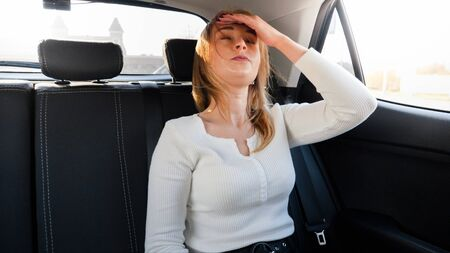 Portrait of upset young woman holding hand on her forehead because of the headache while riding in taxi car