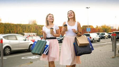 Portrait of female friends with shopping bags walking on car parking at big shopping mall