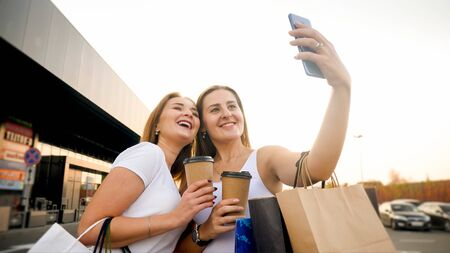 Portrait of two smiling girls making selfie with coffee cups and paper bags at big shopping mall