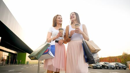 Portrait of two female shopaholics with lots of paper shopping bags standing on car parking at big mall 版權商用圖片