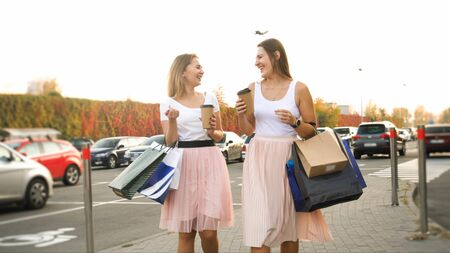 Two happy laughing girls with paper bags walking on car parking and drinking coffee