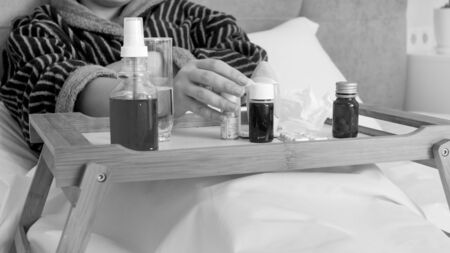 Black adn white portrait of sick woman taking medicines fom wooden tray in bed