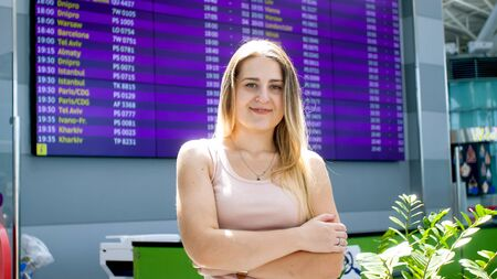 Portrait of smiling young woman in modern airport terminal looking in camera Foto de archivo