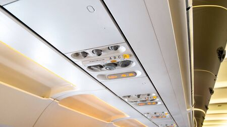 Closeup image of ceiling in airplane with lights and controls