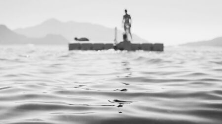 Black and white image of people resting on the floating platform in the sea. 版權商用圖片