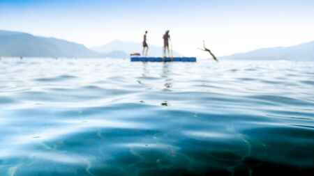Blurred photo of children jumping from the pontoon into the sea water. 版權商用圖片