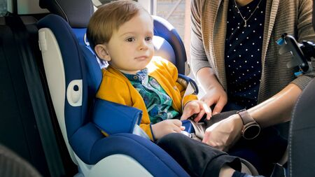 Portrait of cute baby sitting in car safety seat