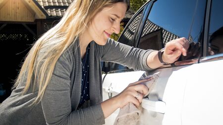 Portrait of smiling female driver polishing her car with cloth Archivio Fotografico