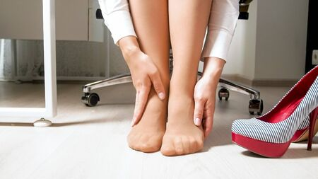 Yougn woman feeling pain in legs and feet after hard working day in office Reklamní fotografie