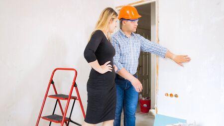 Junge Geschäftsfrau im Gespräch mit männlichen Bauunternehmern, die Haus im Bau bauen
