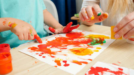 Closeup of adult and child drawing with hands and fingers using colorful paint on white paper. Concept of creative education and art skills development