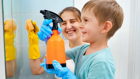 Little toddler boy applying chemical detergent from spray while washing bathroom mirror with mother. CHildren and adults doing housework and cleanup at home Stok Fotoğraf